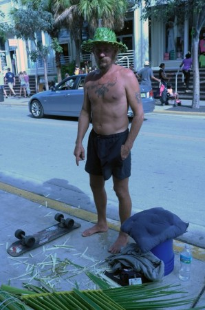 Cool bums populate the street, this skateboard dude makes palm-frond hats.