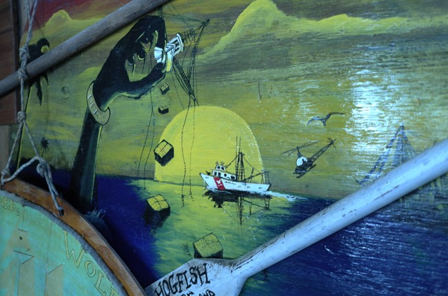 So let's find some real art… I went in search of Monkey Tom, the local hobo artist who's lived here since the 60s. I found this painting he did in a bar. It's the long arm of the DEA shaking a local fishing boat down… see the bales of pot falling out of the fishing boat?