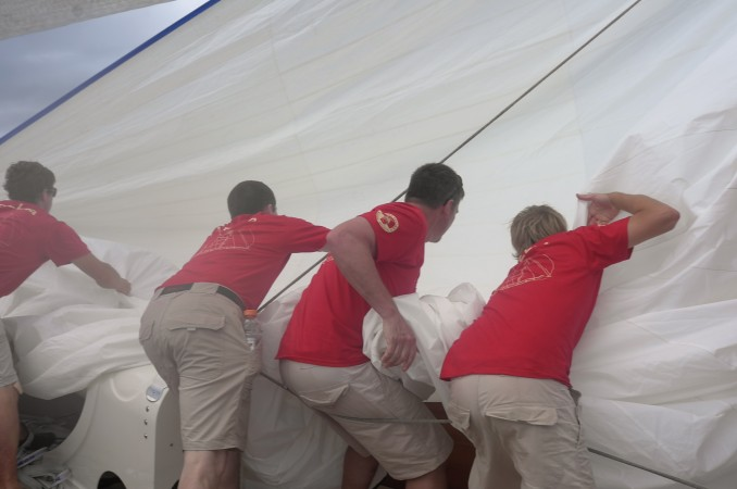 The crew of the schooner Adela shakes out the sails on warmup day.