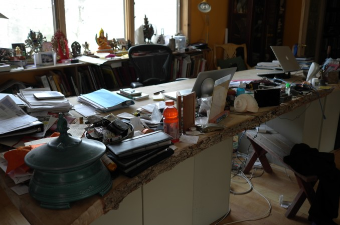 His desk, it's a little messy, a slice of a big tree sitting on file cabinets- really nice design!